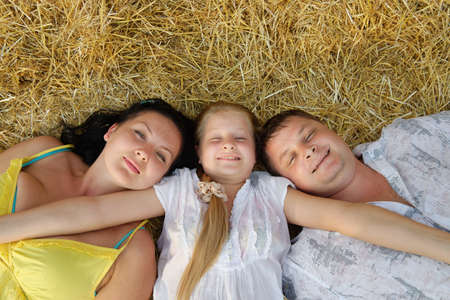 A young family, father, mother and daughter. Lie on hay Stock Photo - 14795784
