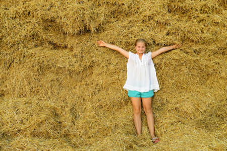 The girl on the background of the large stack of hay photo
