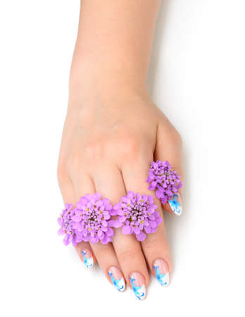 Nail art. Female nails with figure of petal blue color closeup and flower Stock Photo - 14972524
