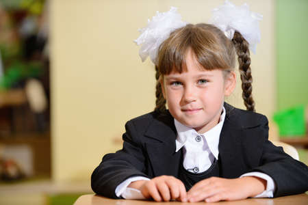 schoolchild with white bows and black suite with white bows. Sitting at a Desk photo