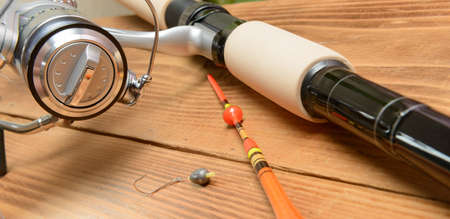 rods: Objects for fishing. The rod with reel, a float, fishing line and hook on a wooden surface
