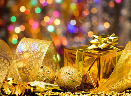 holiday lighting: Gold Christmas decorations. Boxes, ribbons, stars, bells on the bokeh background