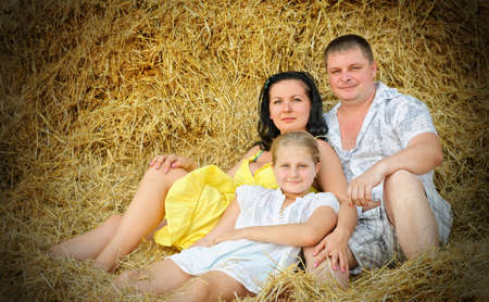 A young family, father, mother and daughter. On the background of the large stack of hay Stock Photo - 15112151