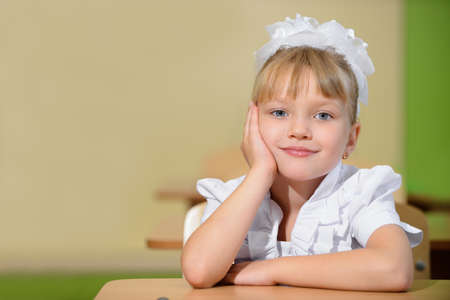 Happy schoolchild with white bows. Sitting at a Desk