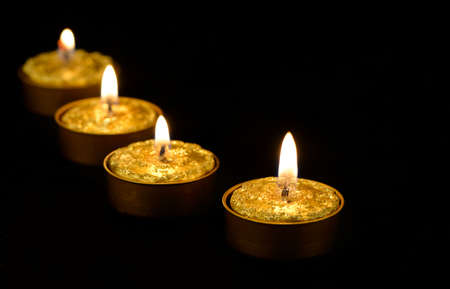 candle lights: Golden burning candles on a black background.
