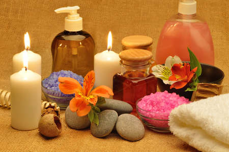 Object for the spa. Candles burning, pebble, a Lily, a bottle with oil, liquid soap, and more. photo