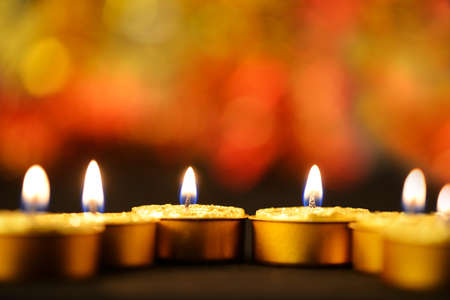 Golden burning candles bokeh blured background