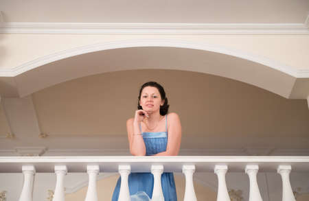 A beautiful woman in a blue dress. The picture on the balcony