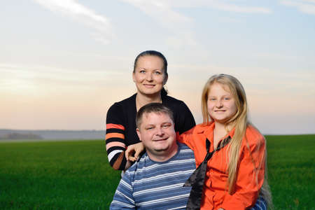 Happy young family. The green field and picturesque sky Stock Photo - 15757104