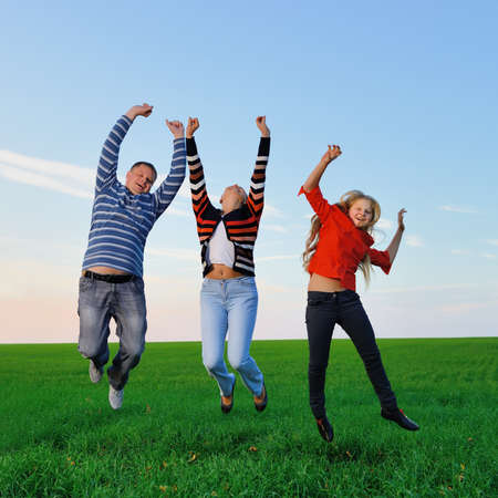 Happy young family jump for joy . The green field and picturesque sky photo