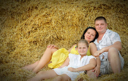 A young family, father, mother and daughter. On the background of the large stack of hay Stock Photo - 15757140