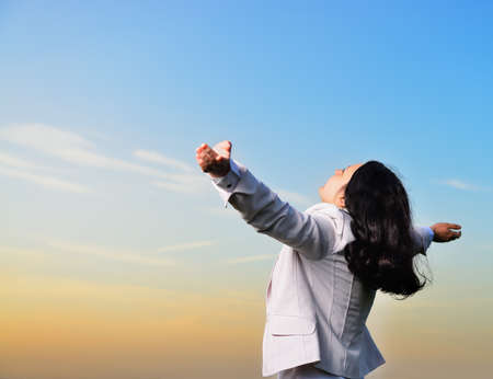 A woman in a business suit with their hands raised . On the background of the picturesque sky Stock Photo