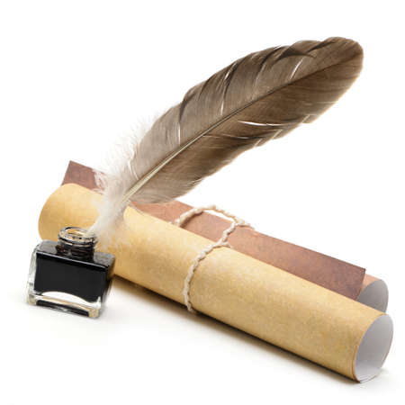 A feather pen, ink,rolls of old yellowed paper. Isolated on a white background. photo
