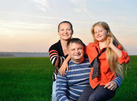 Happy young family. The green field and picturesque sky photo