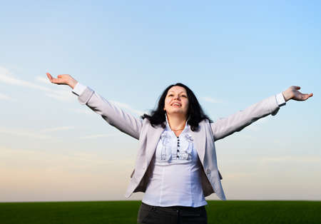 A woman in a business suit with their hands raised . On the background of the picturesque sky photo