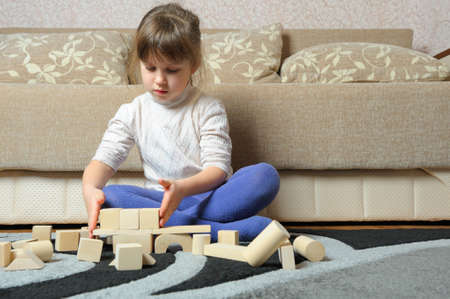 The little girl plays wooden toy cubes. A house room photo