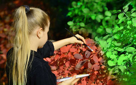 Girl paint in red color of the foliage of trees. The concept of autumn photo