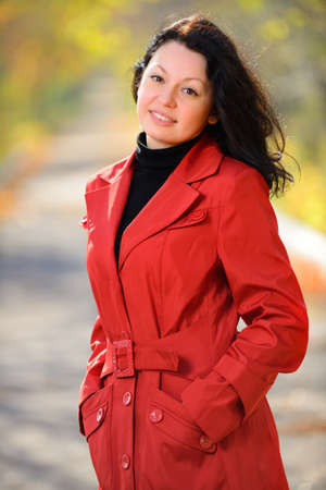 beautiful woman in a red cloak . Autumn Park Stock Photo - 16060944