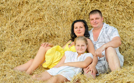 A young family, father, mother and daughter. On the background of the large stack of hay photo