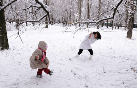 Mum and the daughter play snowballs on the nature photo