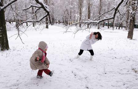 palle di neve: Palle di neve gioco mamma e la figlia sulla natura Archivio Fotografico