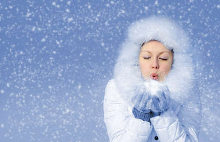 Girl blows off snowflakes from the hand. Blue sky, falling snow Stock Photo
