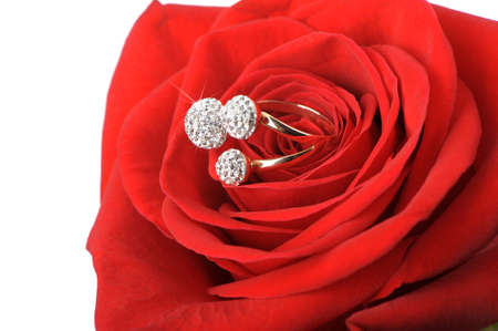 Red rose with a ring with jewels. Isolated on white photo
