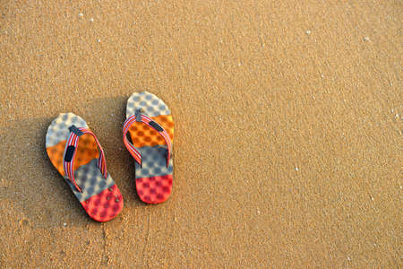 Colorful flip-flops on the sand. The shore of the Indian ocean Stock Photo - 17465952