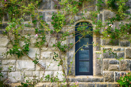 The window in an old house. Walls made of wild stone, plants and flowers on the wall photo