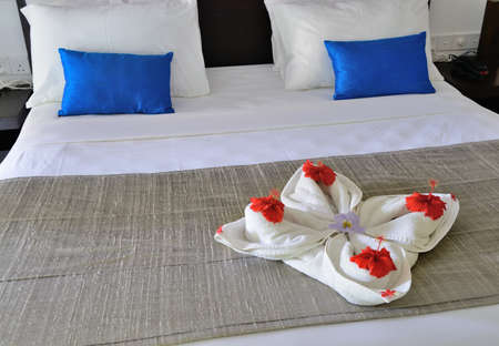 room in a hotel with a decoration of the towel and flowers on the bed . The tropical island of Sri Lanka