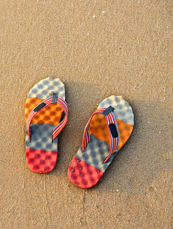 Colorful flip-flops on the sand. The shore of the Indian ocean