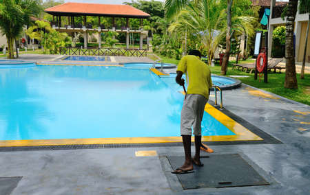 A man cleans the pool. Not recognizable personality