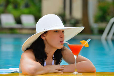 girl with a cocktail at the edge of the swimming pool . Red cocktail with an orange slice. photo