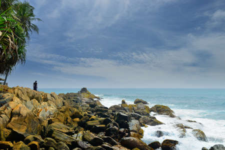 Man on a rocky shore.Beautiful shores of the Indian ocean