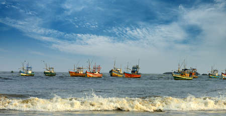 Fishing boats in the ocean . The brightly colored boats moored to the shore of the Indian ocean