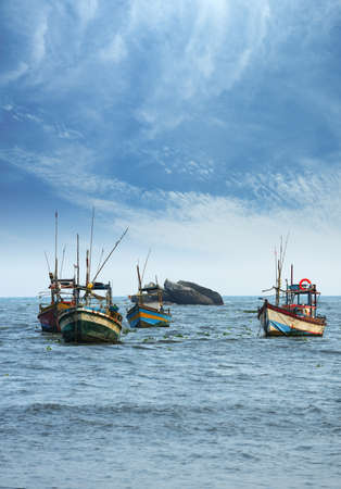 Fishing boats in the ocean . The brightly colored boats moored to the shore of the Indian ocean photo