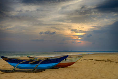 Fishing boats on the shore of the ocean. Tropical sunset