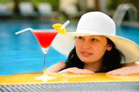girl with a cocktail at the edge of the swimming pool . Red cocktail with an orange slice.
