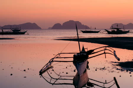 nido: banca on the bay in el nido palawan philippines on beautiful lilac sunset sky