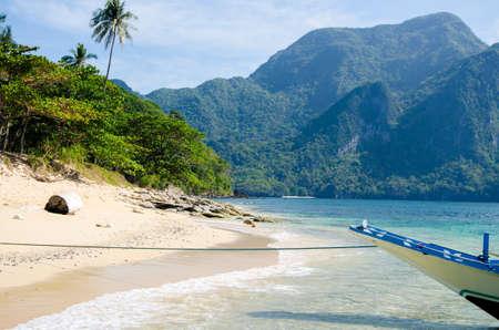 palawan: El Nido, palawan, Philippines - Banca on Dilumacad island, Cadlao on background.