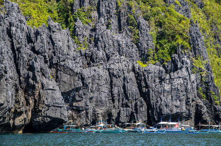 nido: Bancas in front of huge rocks miniloc island. El Nido, Palawan, Philippines Stock Photo