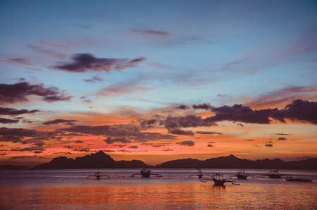 nido: Red Sunset in El Nido, bancas in sea, Palawan, Philippines, vintage look