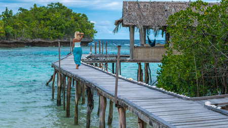 Girl on Pier in front of Bamboo Huts of an Homestay, Gam Island, West Papuan, Raja Ampat, Indonesia