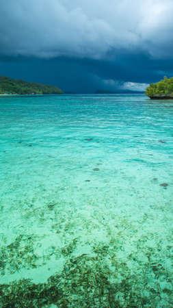 Beautiful Blue Lagoone shortly before Thunderstorm, near Kordiris Homestay, Gam Island, West Papuan, Raja Ampat, Indonesia. Stock Photo