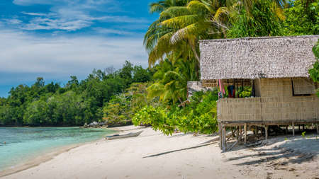 Bamboo Hut under Palm Trees of an Homestay on Gam Island, West Papuan, Raja Ampat, Indonesia. Stock Photo