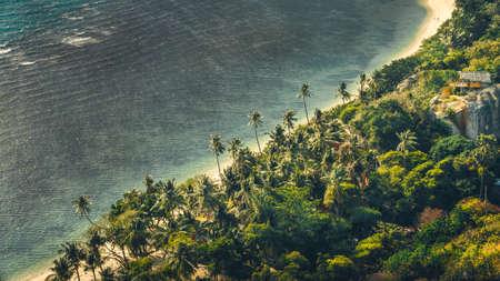 rin: Tropical sandy beach with palms and an hous, gray ocean during a windy day, Haad Rin Beach, Koh Phangan, Thailand