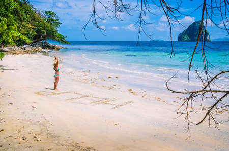Women inscribed Help on the beach with waves and Rock in the background on a hot sunny day, El Nido, Palawan, Philippines Stock Photo