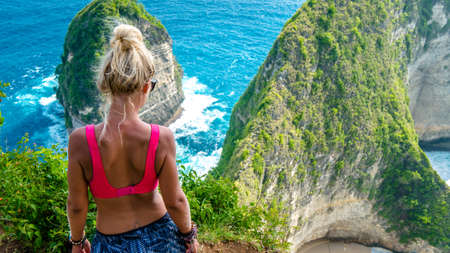 Girl on Cliff at Manta Bay or Kelingking Beach, Nusa Penida Island, Bali, Indonesia