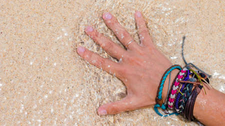 Women Hand with Colourful Wristband Toching Wet Sand on the Beach