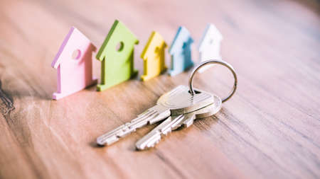 Silver Keychain in front of colourful miniature symbol of houses laying on the wooden surface